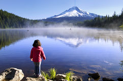 A  baby standing infront of trillium lake Royalty Free Stock Images