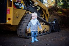 Baby Standing Near the CAT Skid Loader Royalty Free Stock Photo