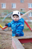 Baby standing by sandpit on playground Stock Photo