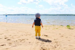 Baby standing on shore of the lake Royalty Free Stock Image