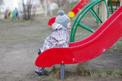 Baby standing by slide on playground Royalty Free Stock Images