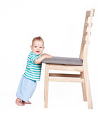 Baby standing up against a chair isolated on white Stock Photo