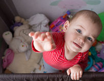 Baby standing up in crib. Blue eyes. Stock Image