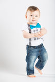 Baby Standing Walking and Smiling. A cute 1 year old is walking in a white studio setting. The boy has a cute expression. He is dressed in Tshirt, jeans Royalty Free Stock Photography