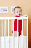 Baby standing in white bed. Baby age of 7 months standing in white bed royalty free stock image