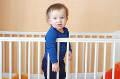 Baby standing in white bed Stock Image