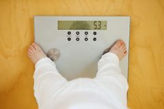 Baby stands on electronic scales that show its weight Stock Photos
