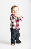 Baby Stands in Flannel and Jeans Holding Hands. A cute 1 year old baby stands in white studio with jeans and a red white flannel looking camera left in Royalty Free Stock Photos