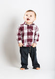 Baby Stands in Flannel and Jeans Looking Left. A cute 1 year old baby stands in white studio with jeans and a red white flannel looking camera left in excitement Royalty Free Stock Photo