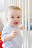 Baby stands by white bed royalty free stock photography