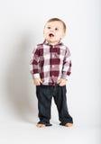 Baby steht im Flanell und in Jeans, die nach links schauen lizenzfreies stockfoto
