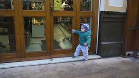 Baby steht nahe der Tür und möchte zum Souvenirladen gehen stock video