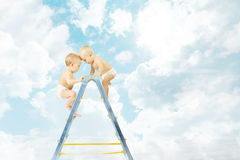 Baby on stepladder fighting for first place over blue  sky Stock Image