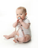 Baby with stethoscope. Adorable baby sitting up wearing and playing with a medical stethoscope, isolated on white Royalty Free Stock Photography