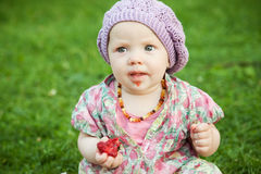 Baby with strawberry in nature stock photography