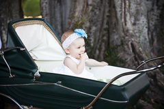 Baby in stroller. Happy baby girl sitting a stroller sucking her thumb Royalty Free Stock Images
