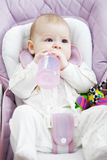Baby in a stroller with bottle Stock Photo