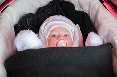 Baby in stroller is dressed and warmly wrapped in freezing winter Royalty Free Stock Photos