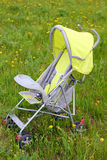 Baby stroller on green lawn Royalty Free Stock Image