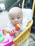 Baby in stroller hold mic toy Royalty Free Stock Image