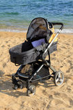 Baby stroller parked on the beach Royalty Free Stock Photography