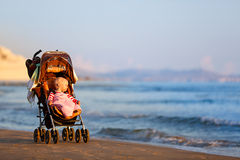 Baby in a stroller on a sandy beach Royalty Free Stock Image