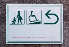 Baby stroller sign and cripple sign with arrow for directions. Stock Photos