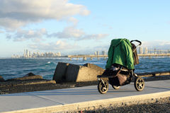 Baby Stroller. Standing at the cape. At the background Surfers Paradise, QLD, Australia Stock Image