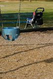 Baby Stroller and Swing. A baby stroller waits near a park bench and infant swing Royalty Free Stock Photos