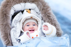Baby in stroller in a winter park Stock Photos