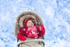 Baby in stroller in winter park with snow Stock Photography