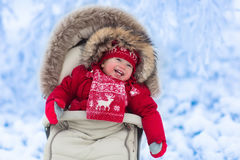 Baby in stroller in winter park with snow. Happy laughing baby in warm red down jacket and knitted Nordic hat and scarf on a walk in a snowy winter park sitting Royalty Free Stock Image