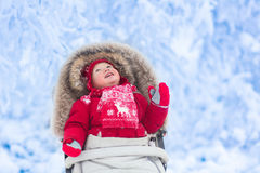 Baby in stroller in winter park with snow Royalty Free Stock Images