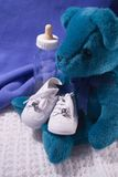 Baby Stuff. Babies shoes, Teddy Bear and Bottle Stock Photo