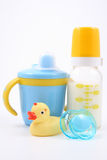 Baby stuff. Bottle of milk baby cup pacifier and yellow duck - baby stuff Royalty Free Stock Images
