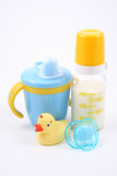 Baby stuff. Bottle of milk baby cup pacifier and yellow duck - baby stuff Stock Photos
