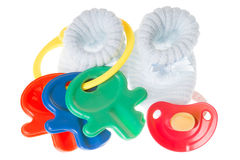 Baby Stuff. Baby toy with pacifier and baby shoes isolated over a white background Royalty Free Stock Images