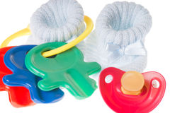 Baby Stuff. Baby toy with pacifier and baby shoes Stock Photo