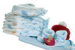 Baby Stuff. Diapers and pacifier with baby clothes over a white background Royalty Free Stock Images