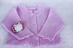 Set for newborn girl with rose knitted blouse and dummy Royalty Free Stock Photo