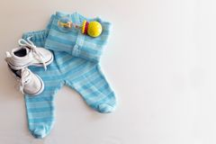 Baby stuff is on a white background. Things for little boy, rattle and shoes. Newborn baby necessities. royalty free stock image