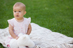 Baby with stuffed toy sitting on blanket at park Royalty Free Stock Photos
