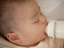 Baby suck milk bottle with eyes closed Stock Photo