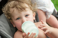 Baby sucking on a bottle of porridge sitting Royalty Free Stock Photo