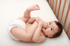Baby sucking his toes. Beautiful baby laying in cot sucking his toes Stock Photography