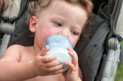 Baby sucks a bottle with milk Royalty Free Stock Photography