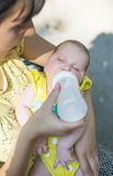 Baby sucks on a bottle. Baby in mothers hands Stock Photo