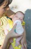 Baby sucks on a bottle Stock Photo
