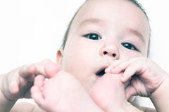 Baby sucks his toe. Portrait of a child sucks his toe Royalty Free Stock Images