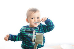 Baby sugar grinder. The child with a spoon eating sugar Stock Images